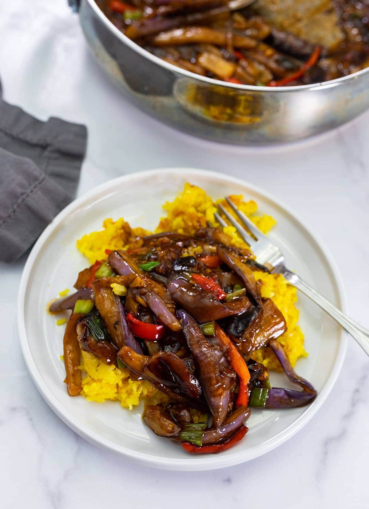 eggplant in garlic sauce over rice on a white plate