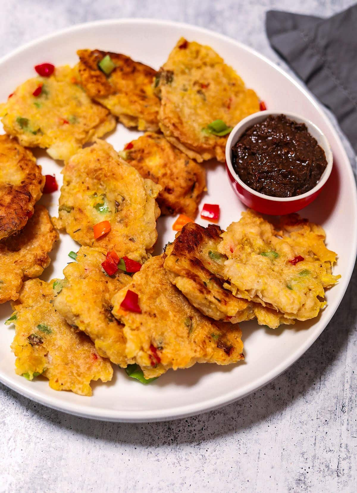 Plantain fritters overlay in a white plate with jerk sauce in a small bowl