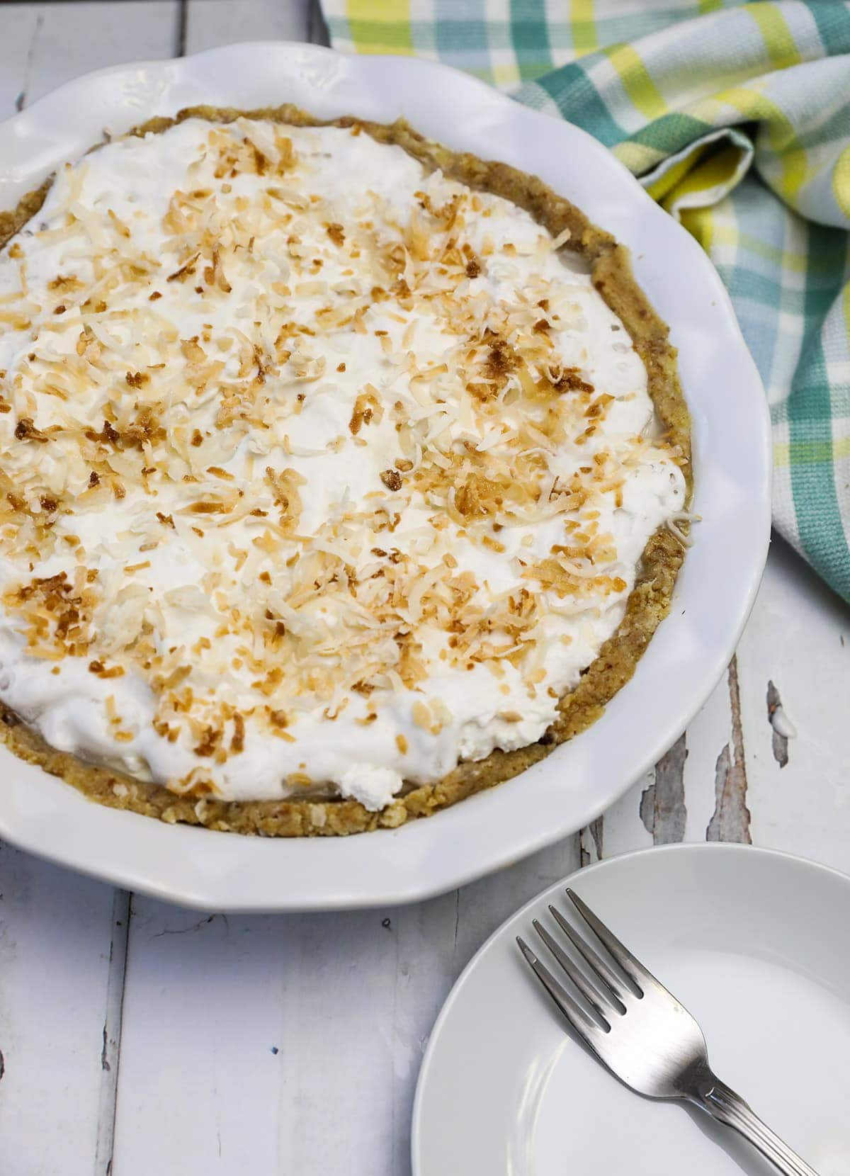 overlay coconut pie on a white wooden board