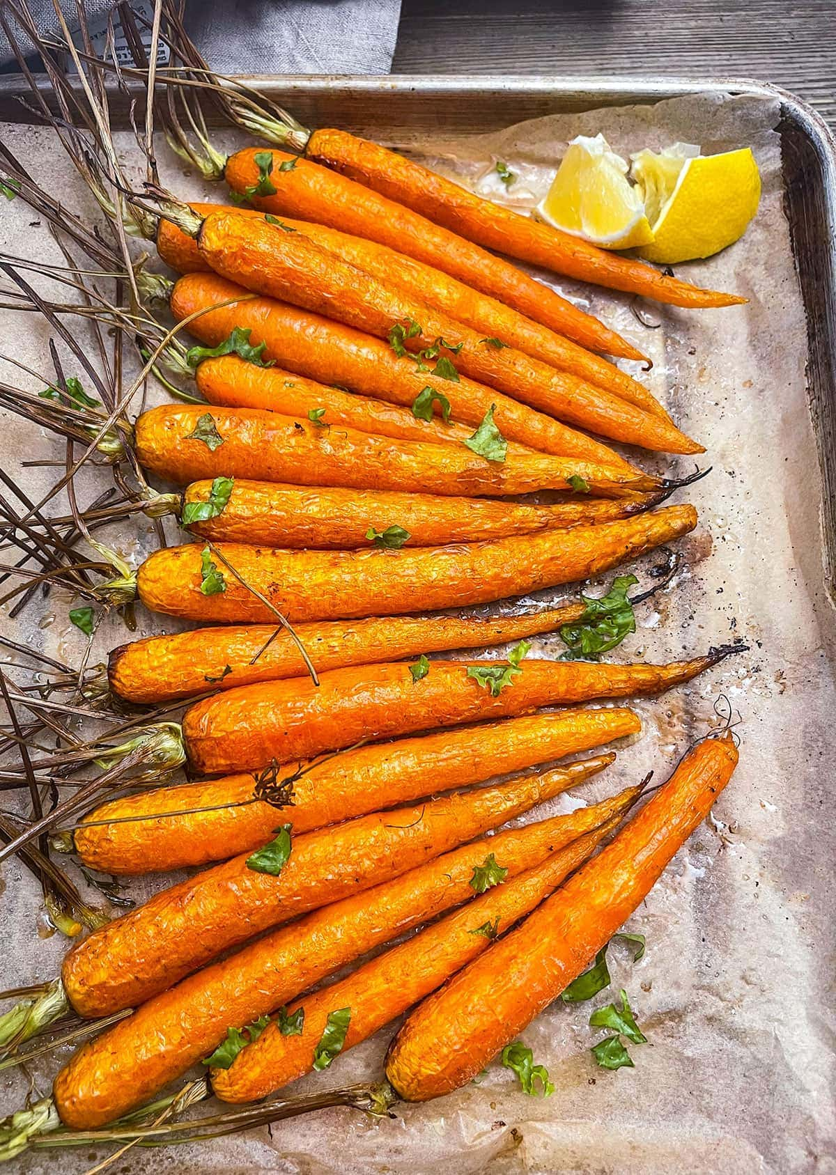 a sheet pan with parchment paper and a row of air fried carrots garnished with parsley and lemon