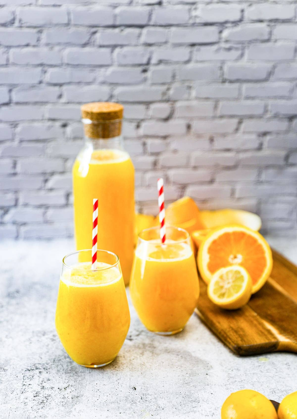orange lemonade in glass flask and glasses with sraw on a grey background