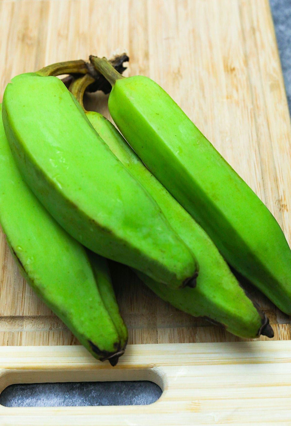 green bananas on cutting board