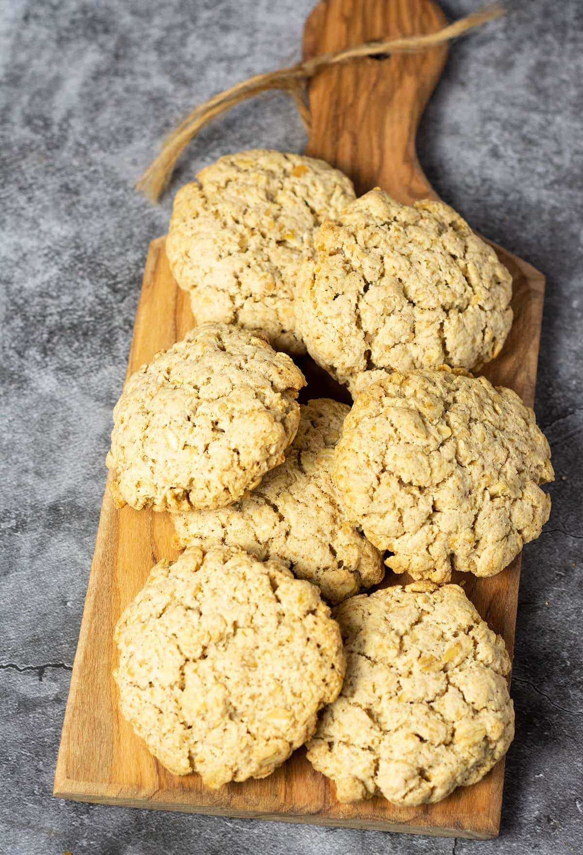Overlay Vegan Oatmeal Cookies on a wooden cutting board on a grey background