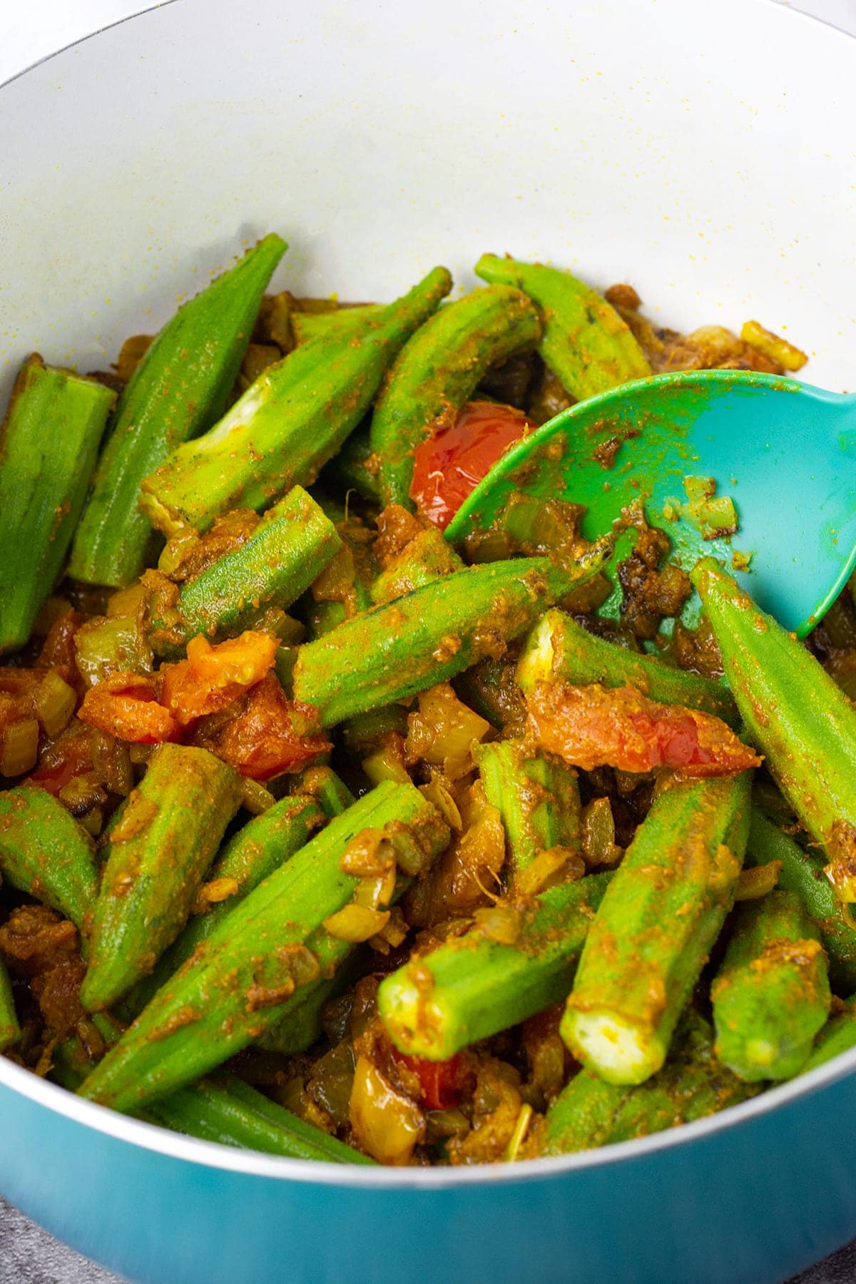 sauteed okra with onion, garlic, ginger, tomato in a large blue pot with a blue spoon