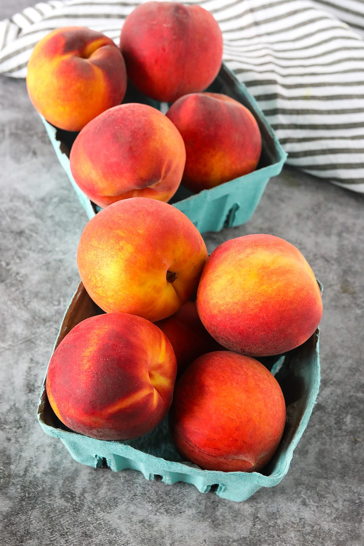 peaches for air fryer peaches in 2 green paper baskets on a grey marble background
