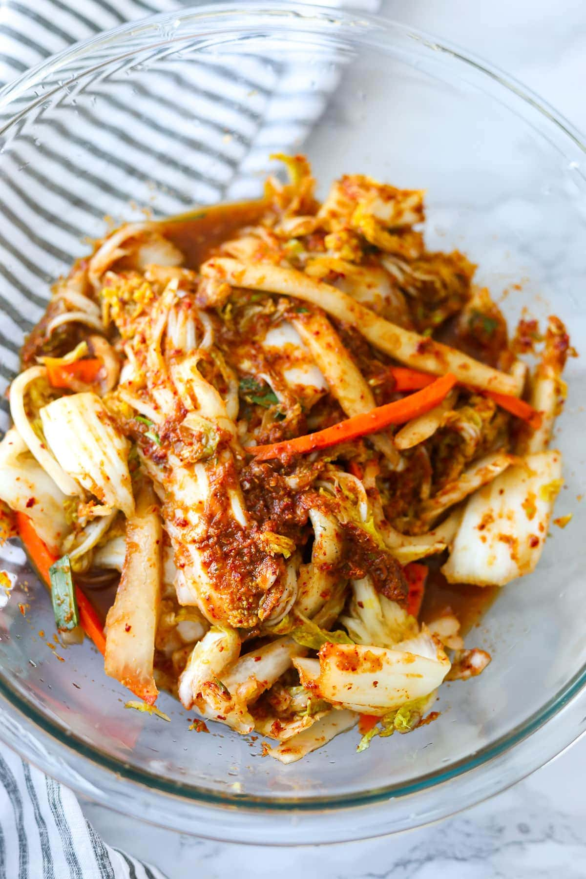 kimchi with paste in a glass bowl with stripe napkin
