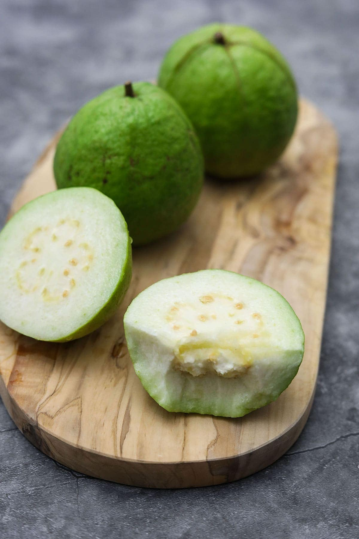 white guava on cutting board, one cut open to show its white flesh