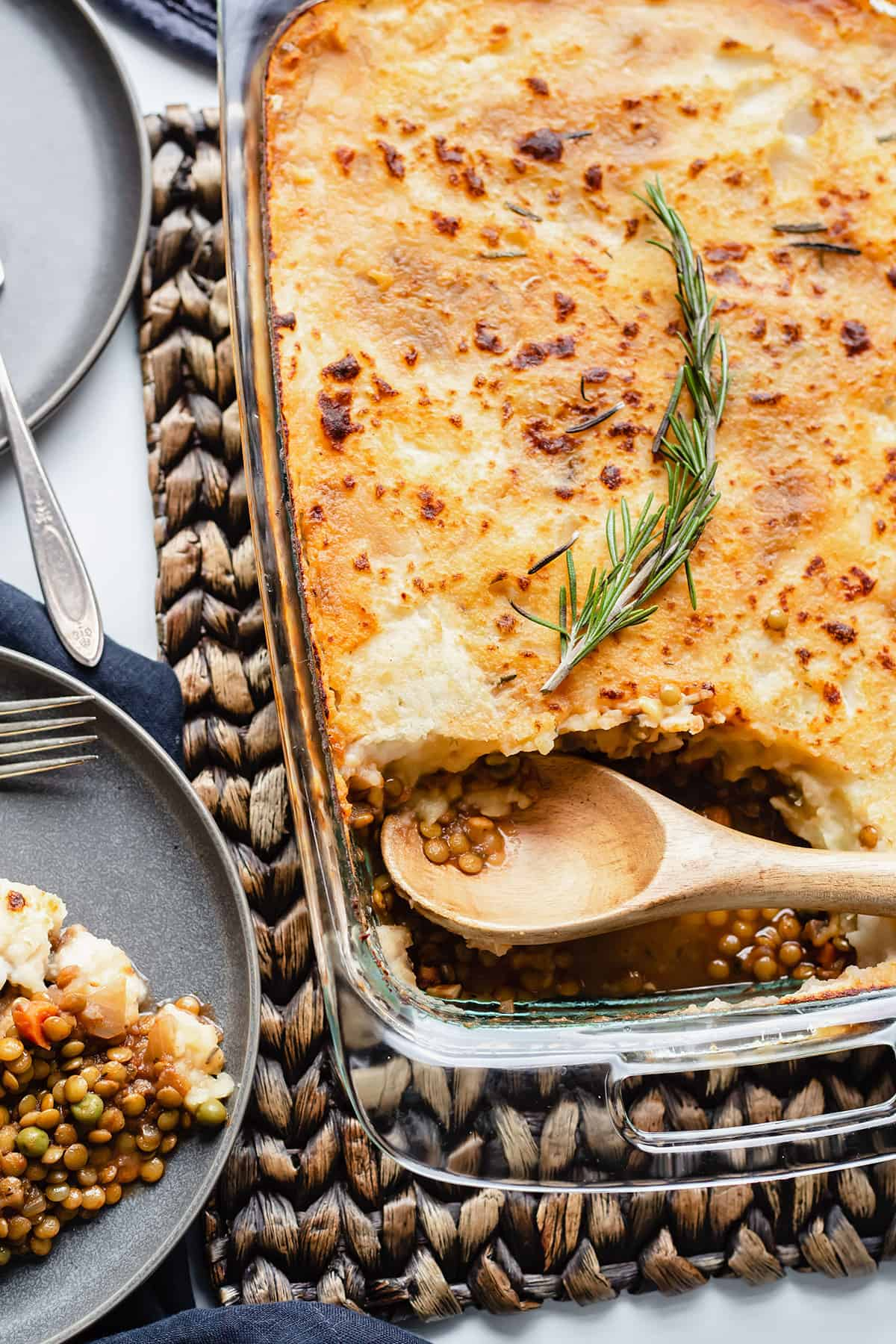a shepherd's pie in a glass casserole dish with a piece taken out and a wooden spoon sitting in it