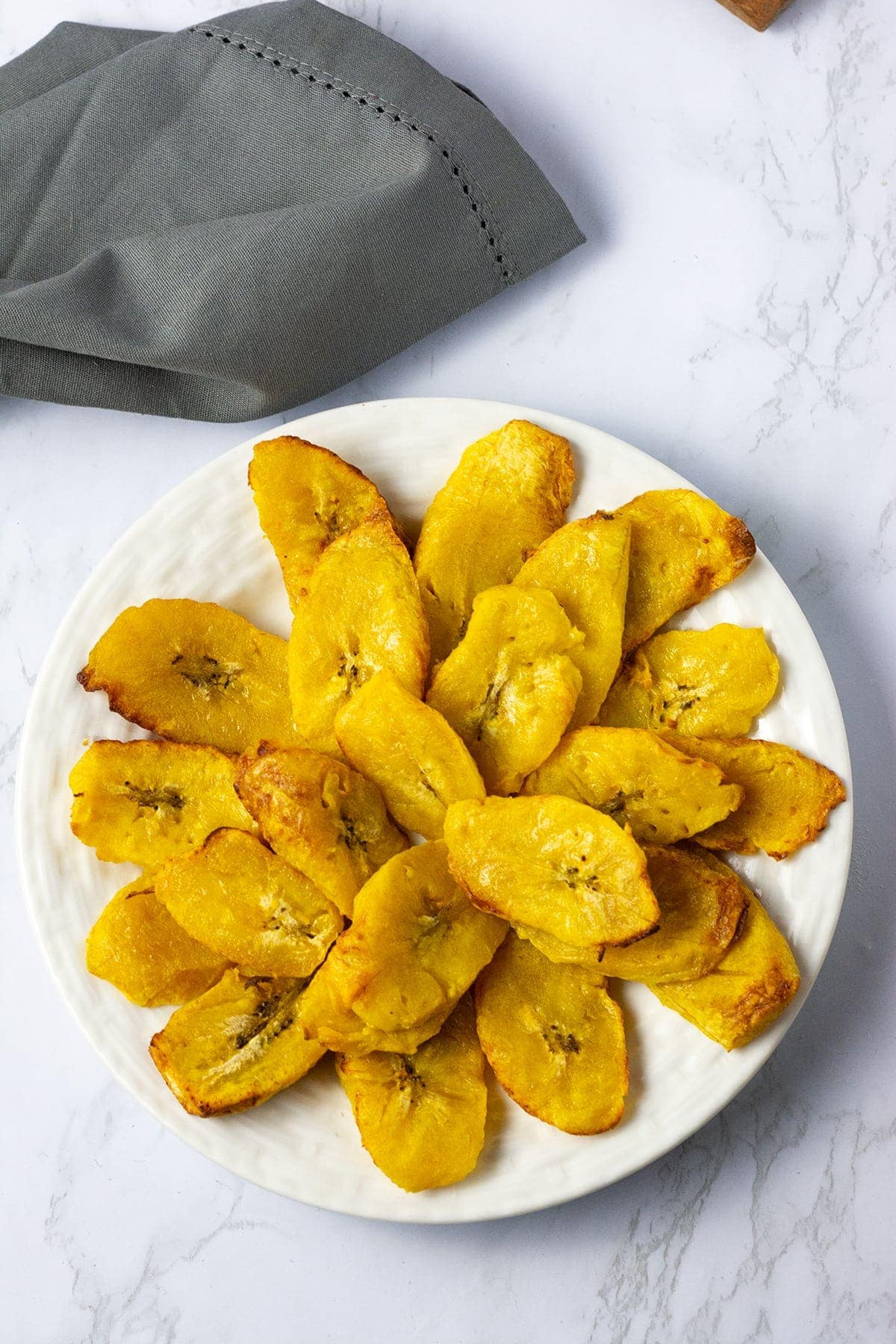 air fried plantains in a pile on a white plate