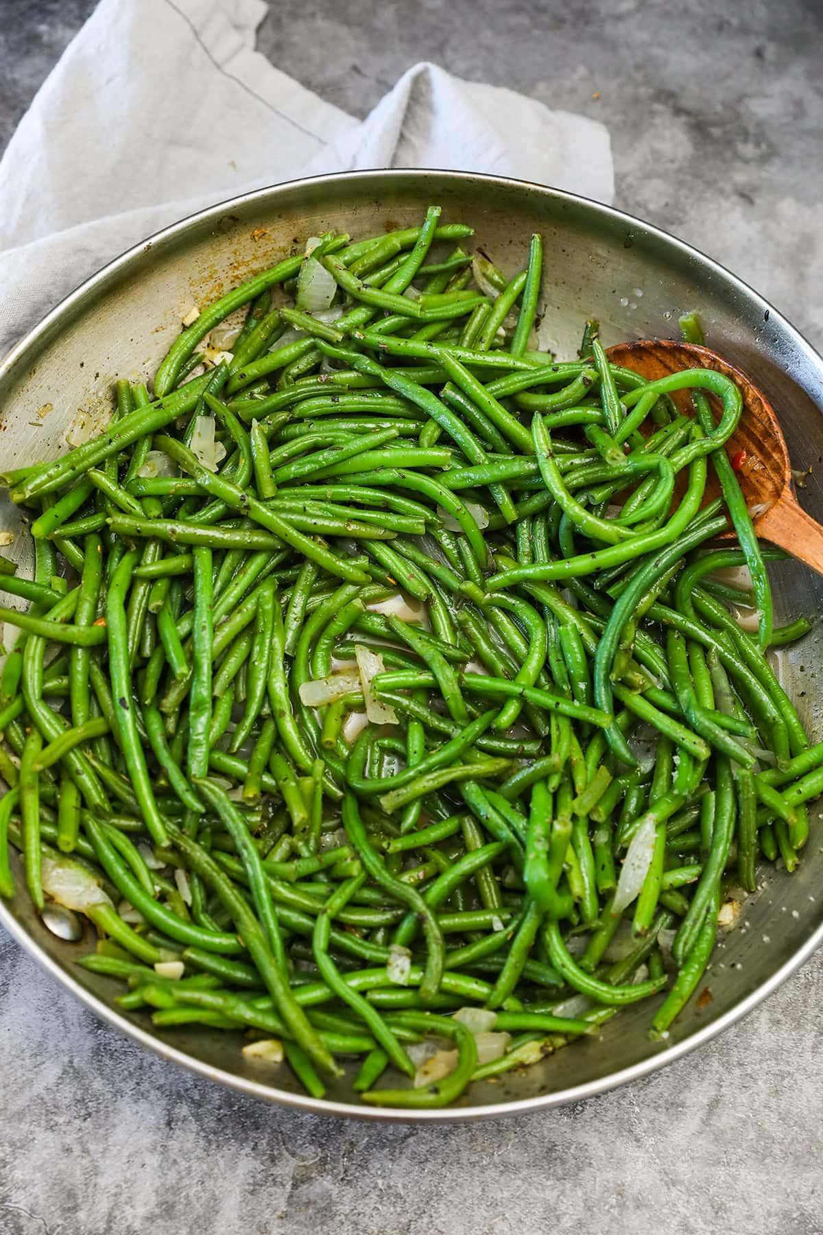 frozen green beans in skillet on grey background