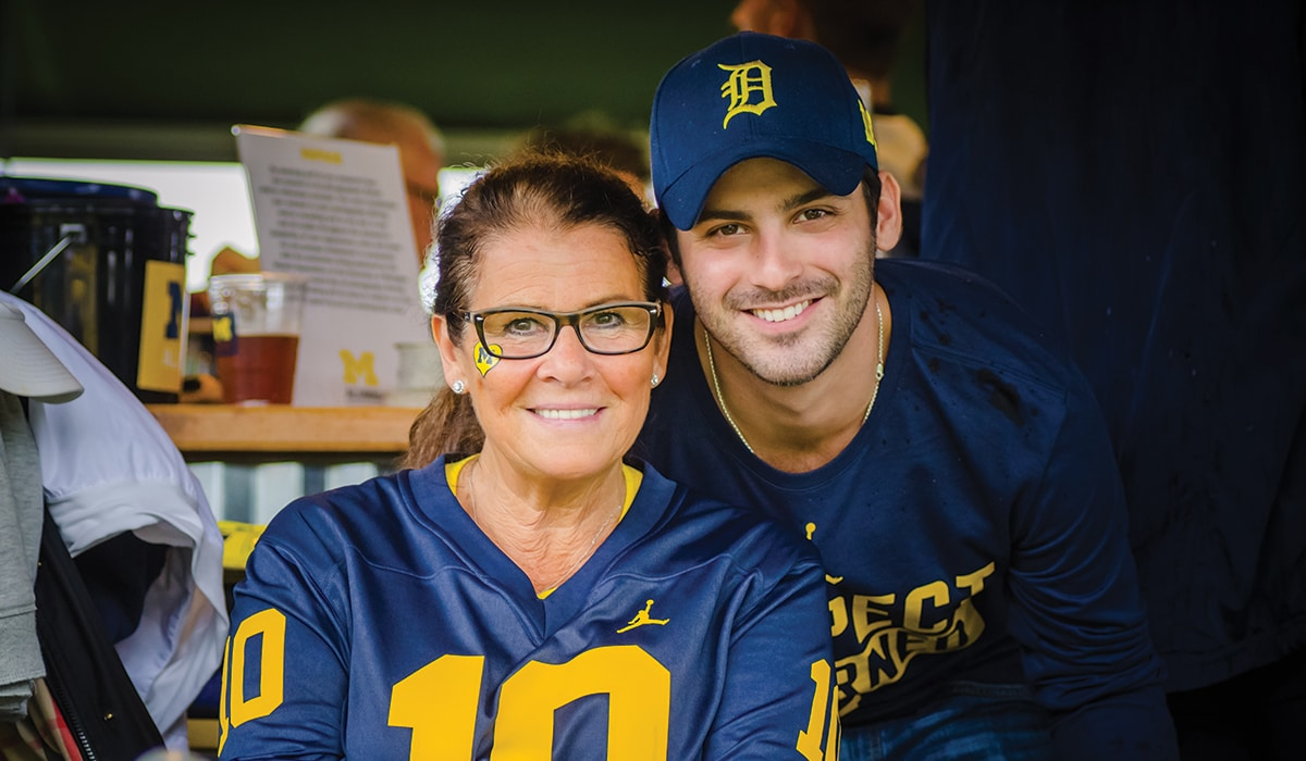 Two people wearing Michigan gear pose for a picture