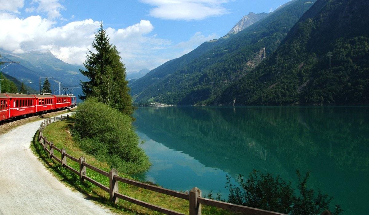Switzerland: July 2012, Swiss Mountain Train Bernina Express at Lake of Poschiavo.