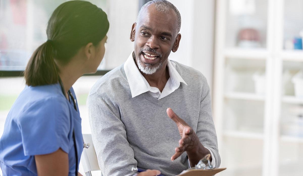 Senior Man Talking With Young Female Nurse