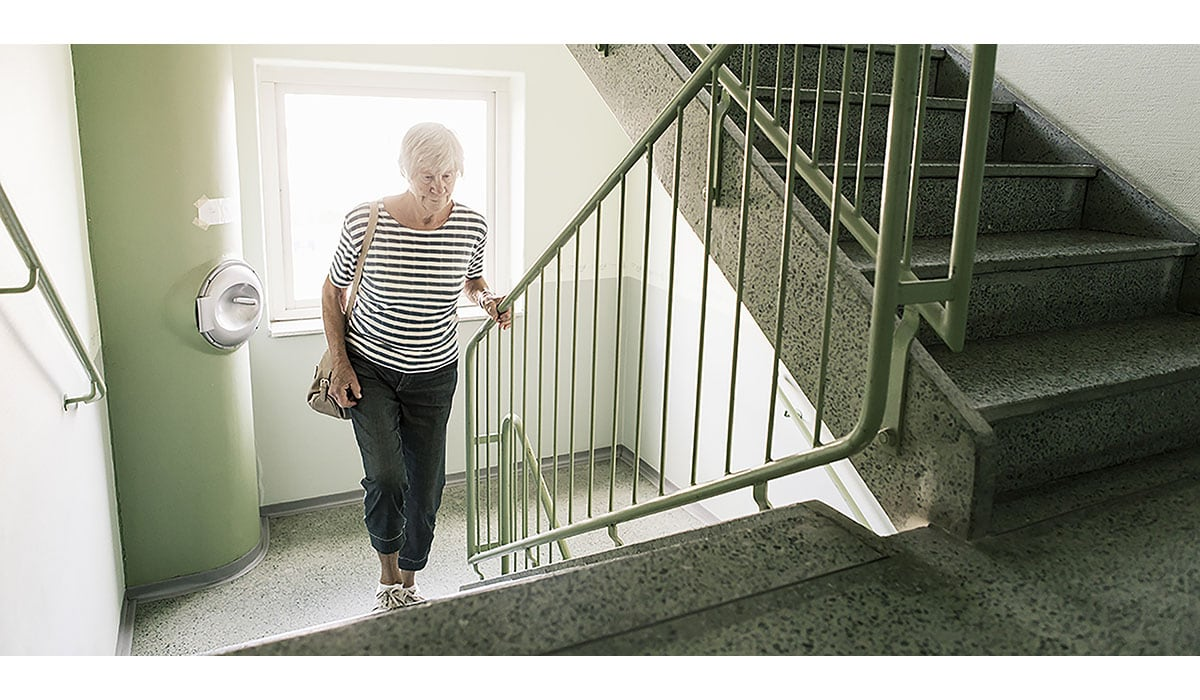 Senior Woman Walking On Staircase In Apartment Building