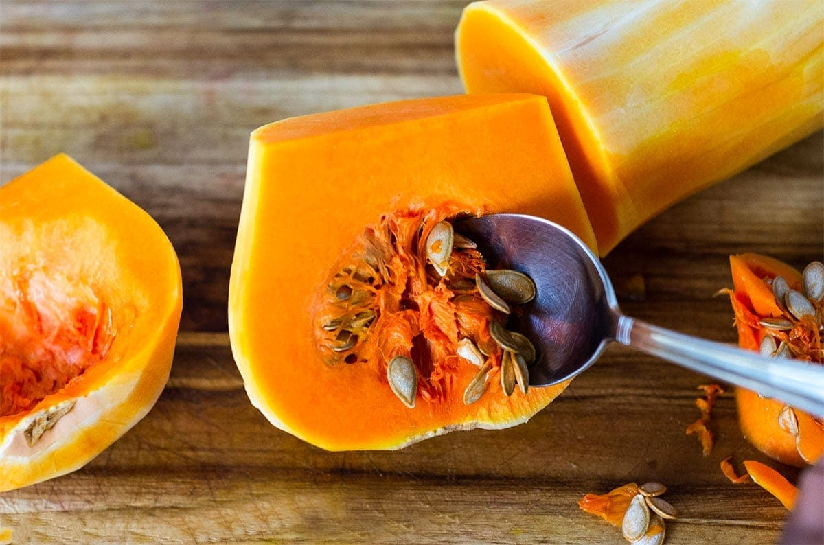 butternut squash on a wooden background being scoope with a spoon