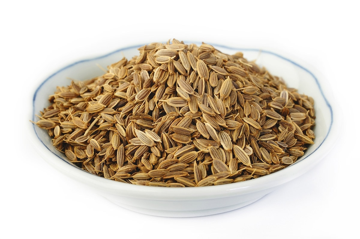 dill seeds in a white bowl on a white background