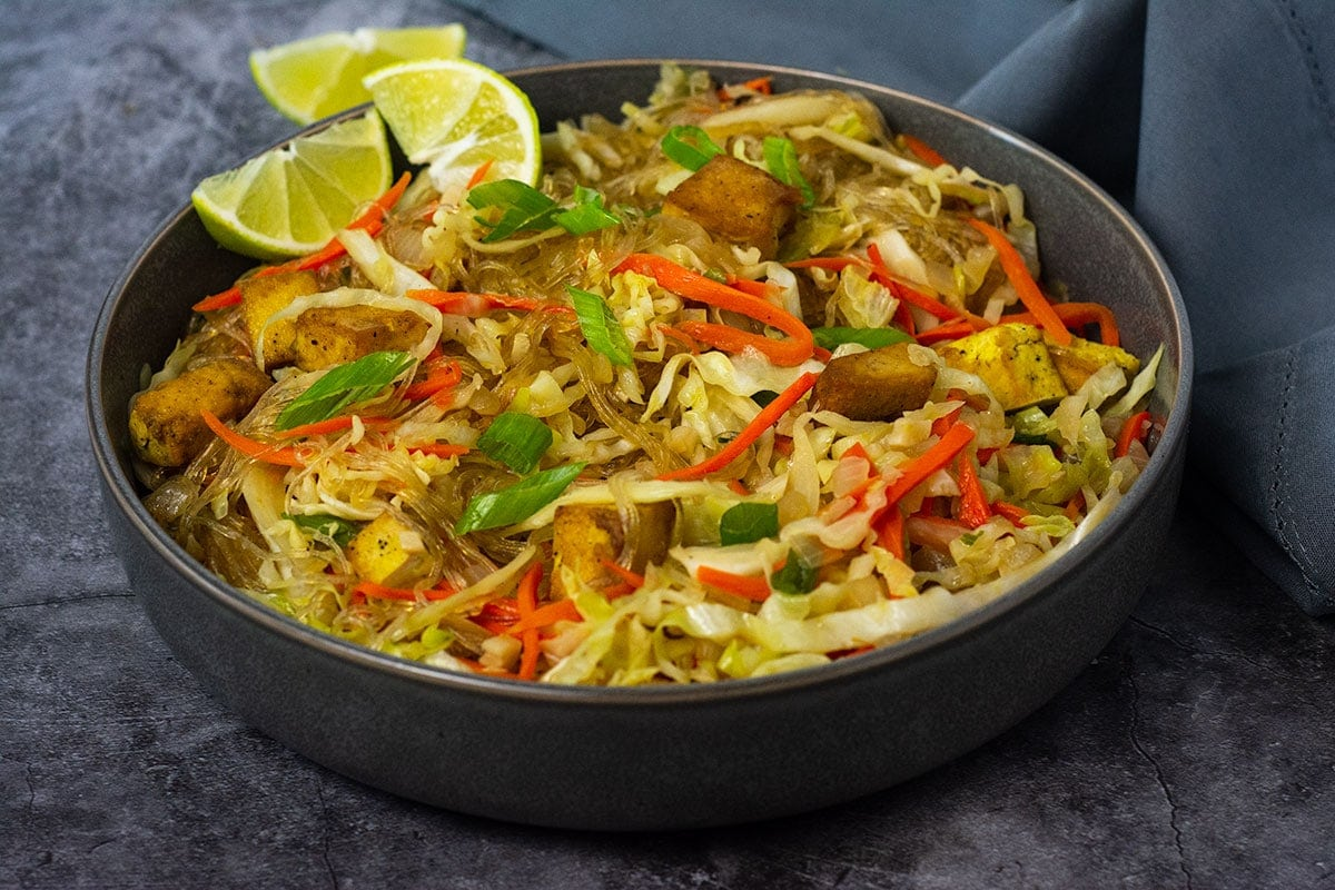 straight on vegan pancit bihon in a grey bowl garnished with green onions and lime on a grey background