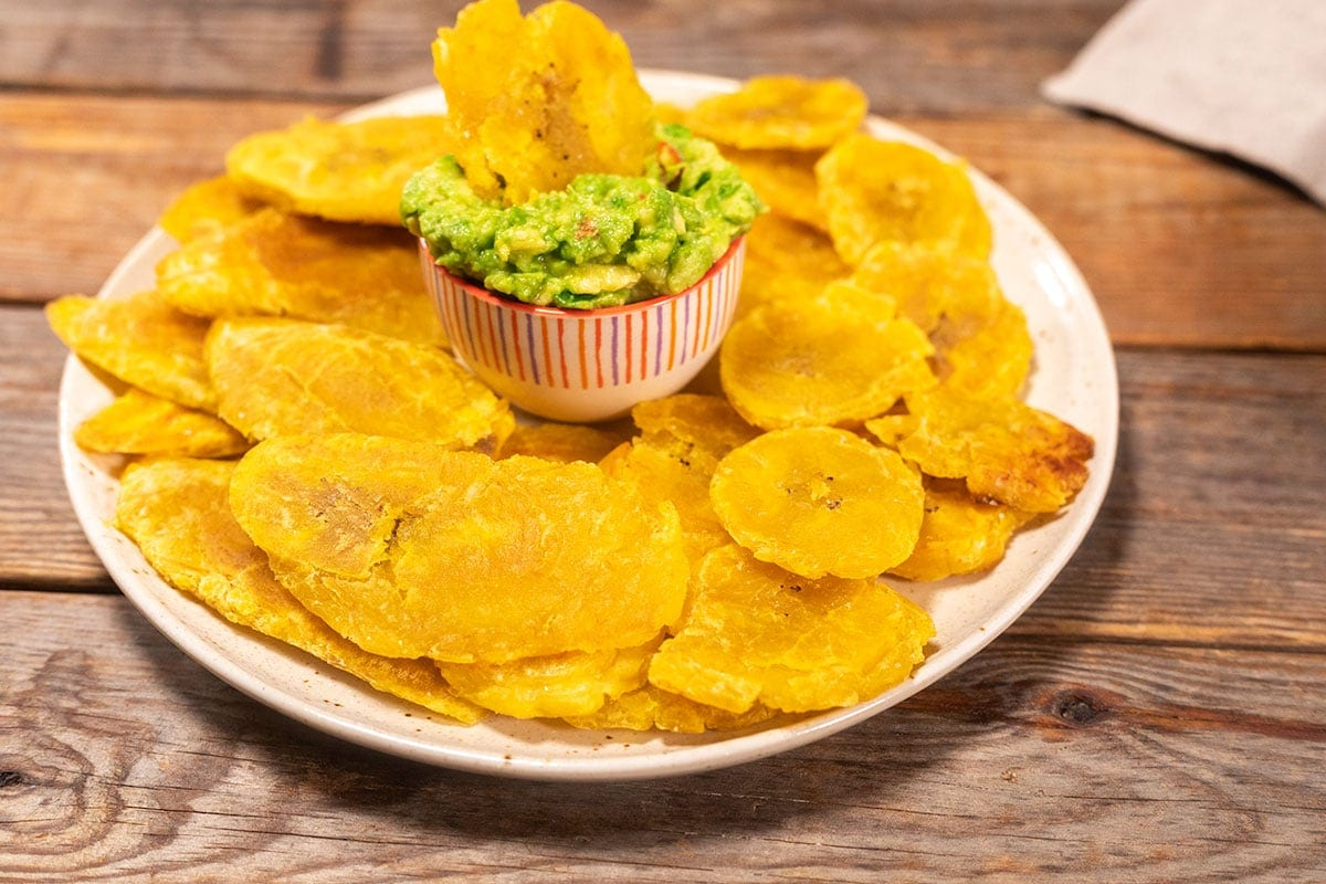 Overlay of air-fryer tostones on a spotted plate with a wooden background