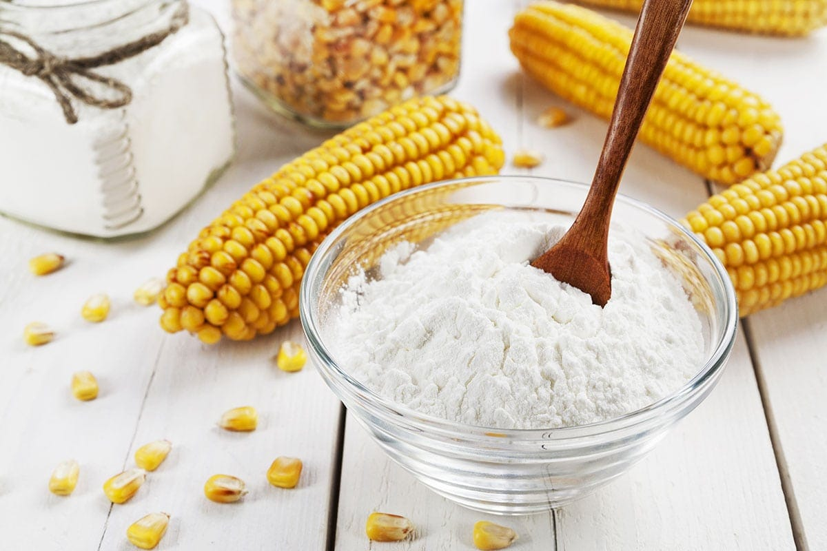 cornstarch in a glass bowl with a wooden spoon on a white background with dried corn ears and kernels. A great Arrowroot Flour Substitute