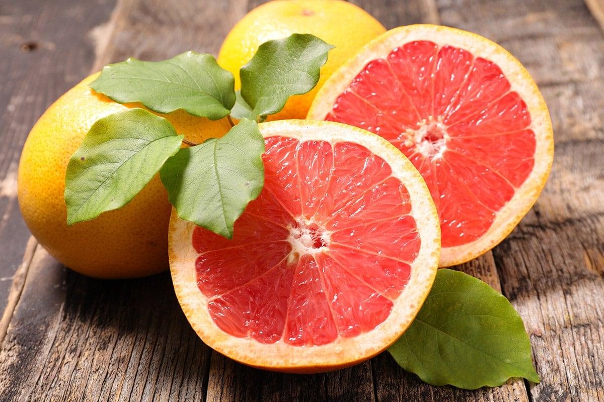 Grapefruit cut in halves on wooden background