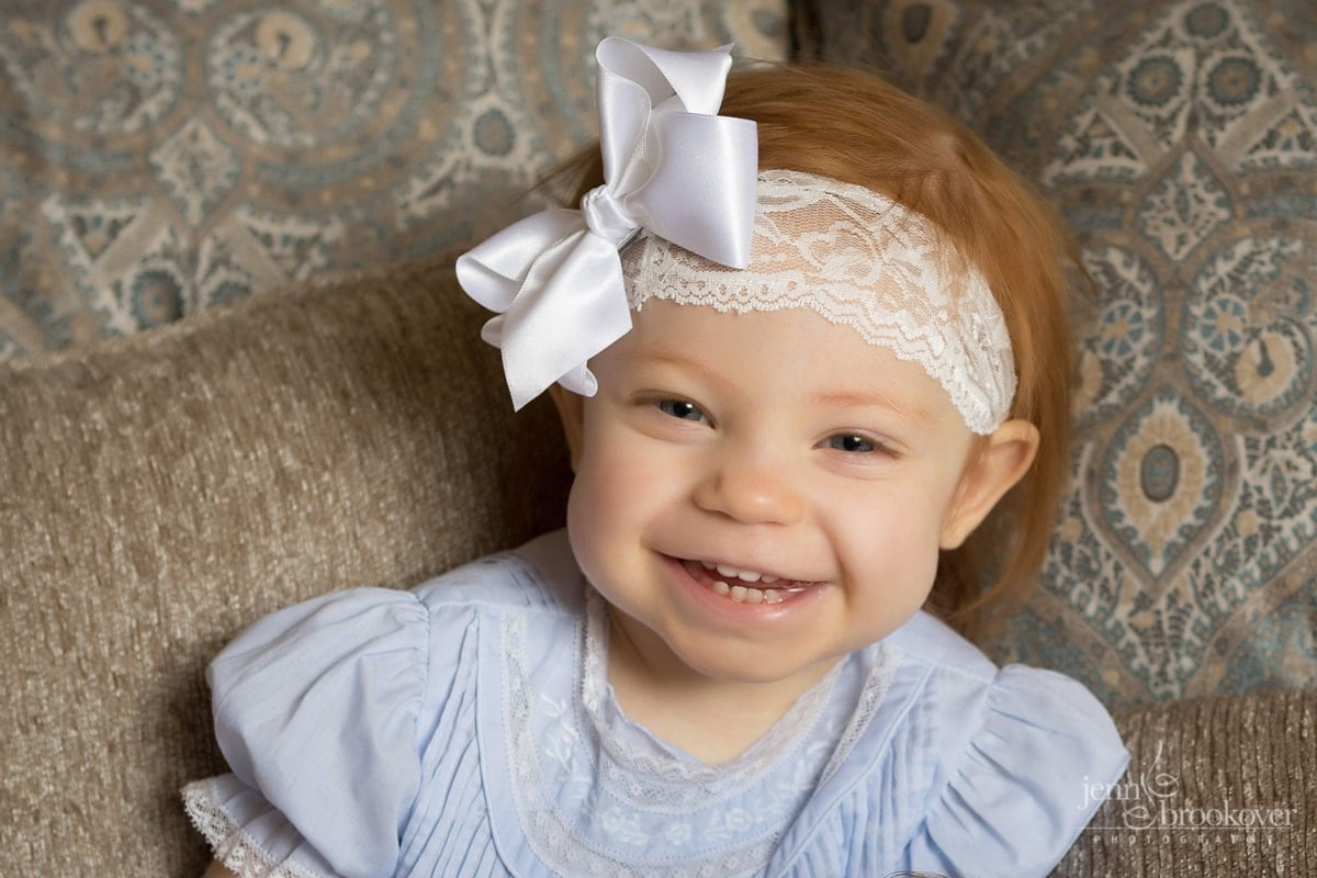 big sister smiling and laughing in a big white bow
