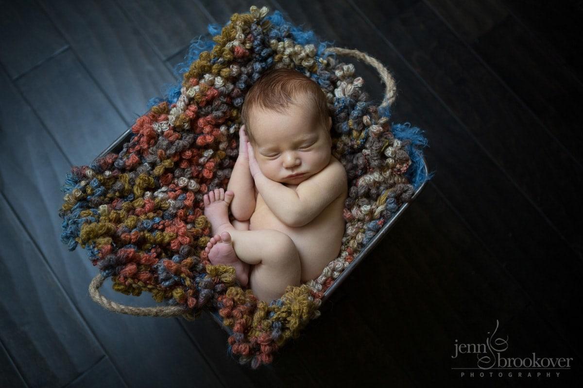 newborn san antonio on orange, blue and brown blanket on wood floor