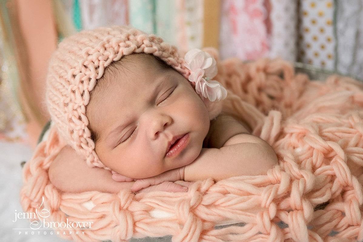 newborn in peach handmade hat with banner by Nursery Couture taken in San Antonio by Jenn Brookover
