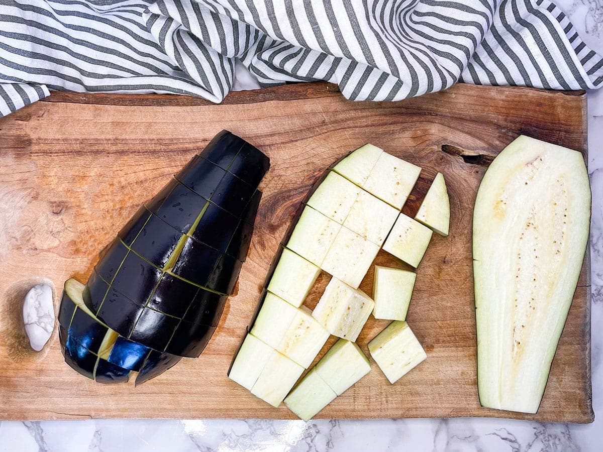Eggplant diced on cutting board on a white backgrounbd