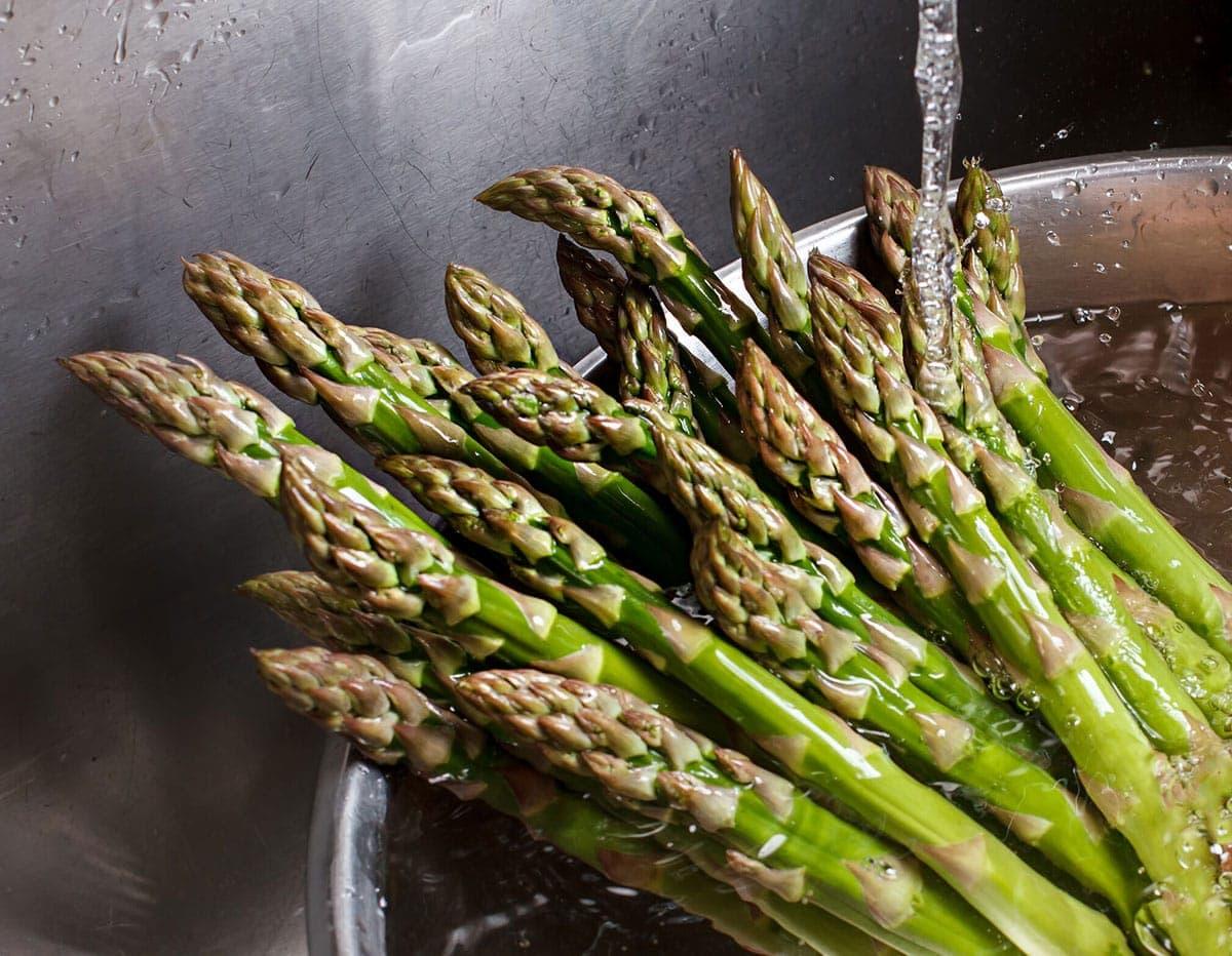 washing asparagus under running water