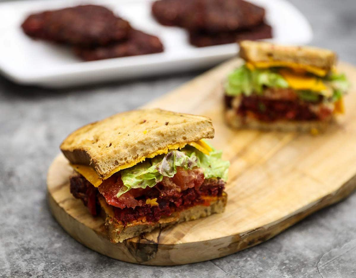 beet burger recipe on wooden board on grey background with a white platter with beet burgers in the background
