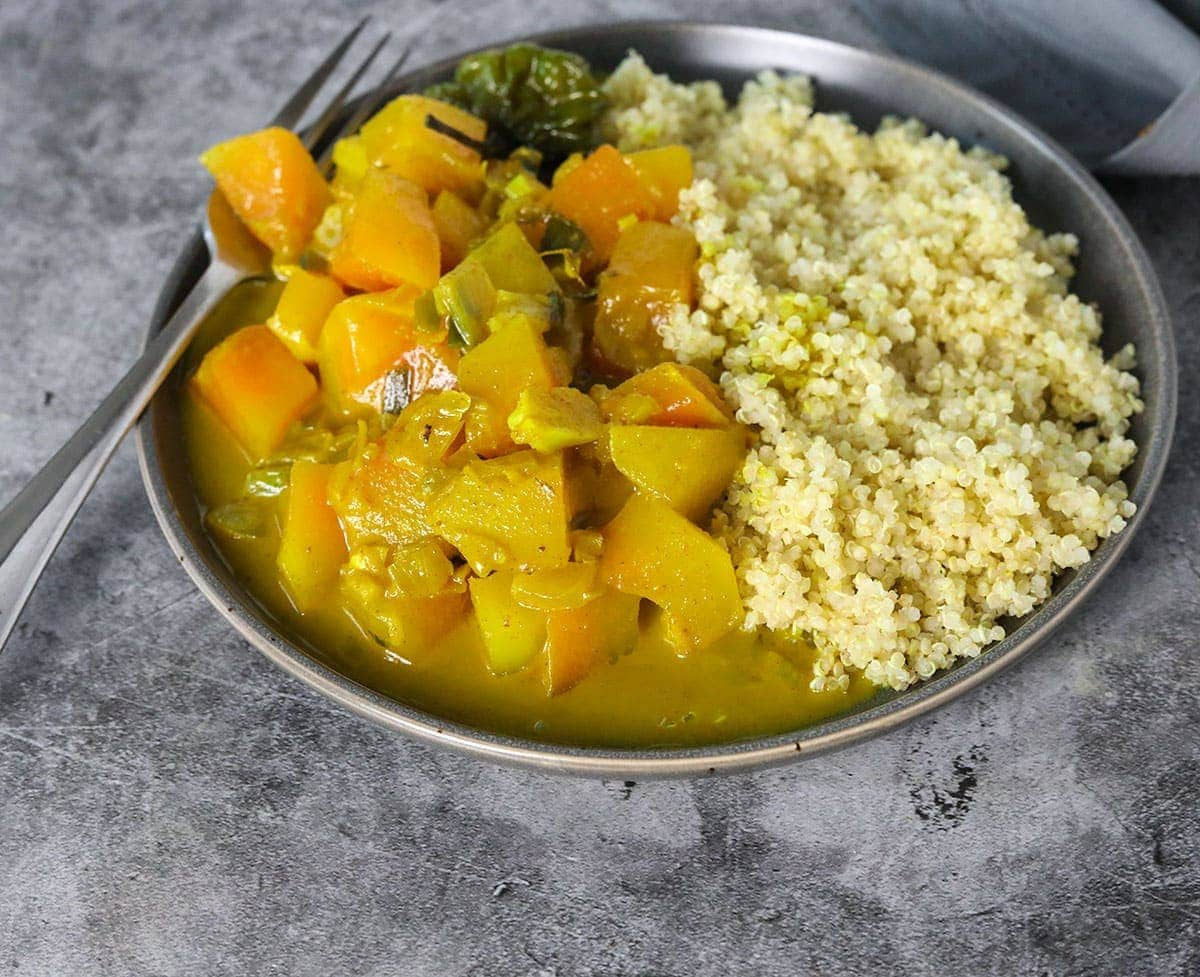 close up image of curry papaya in a grey plate on a grey background