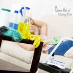 woman recling on sofa in background with cleaning supplies in foreground