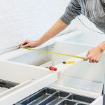 woman measuring and installing base cabinets