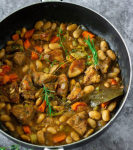 White bean stew with jackfruit, carrot, potatoes in a black skillet