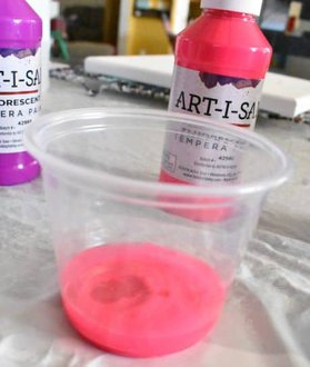 water poured into tempera paint in clear plastic cup