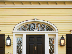 a black custom traditional front door with decorative transom and sidelights