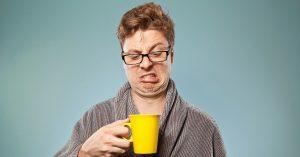 man looking down at his coffee mug making a grimace