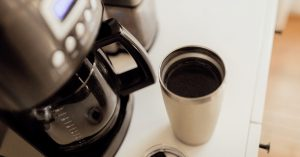 4 cup coffee maker and a cup of coffee