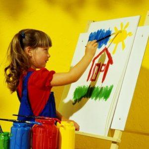 Девочка рисует дом на мольберте