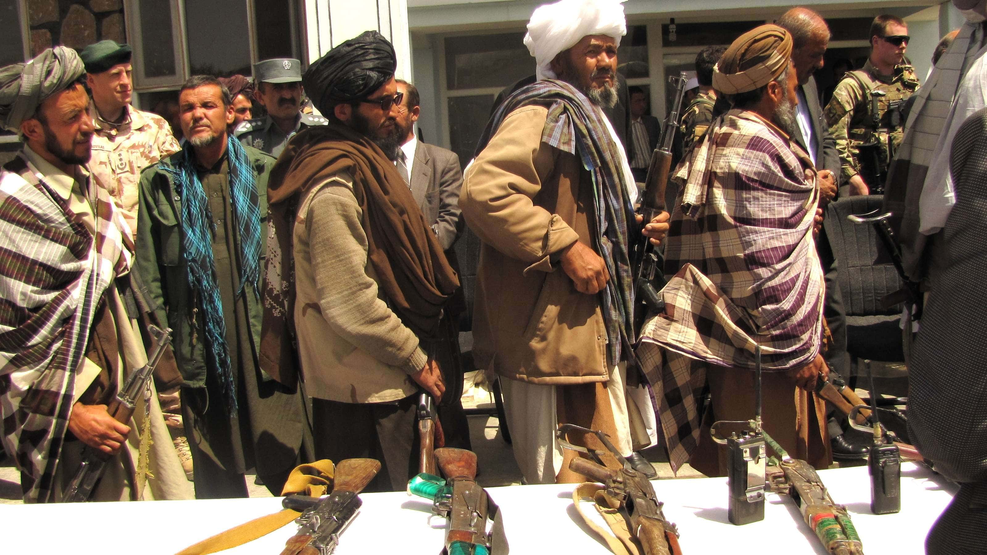 Former Taliban fighters line up to hand over weapons to the Afghan government during a reintegration ceremony in the Ghor province on May 28, 2012. (Image Credit: U.S. Department of Defense/Lt. Joe Painter)