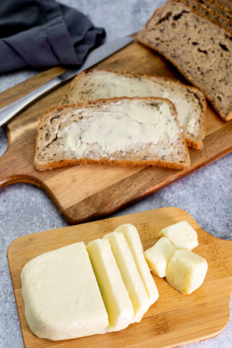 Vegan butter overhead image cut in slices on a cutting board, some spread on slices of bread