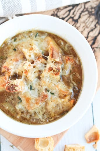 french onion soup in a white bowl with cheese melted on top