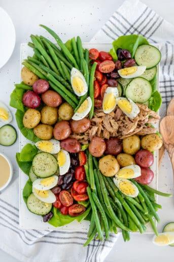 Nicoise salad with green beans, tomatoes, potatoes, cucumbers, tuna, and hardboiled eggs