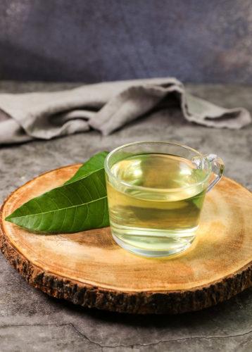 mango tea in glass cup on wooden board