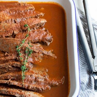 Braised beef brisket in a rectangular serving dish, with kitchen tongs on the right