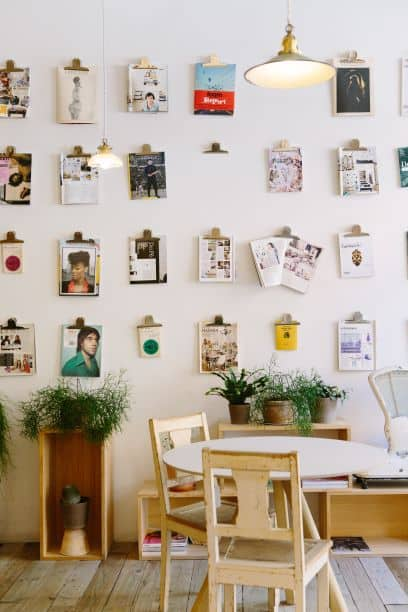 multitude of clips holding art on wall in room with table and chairs