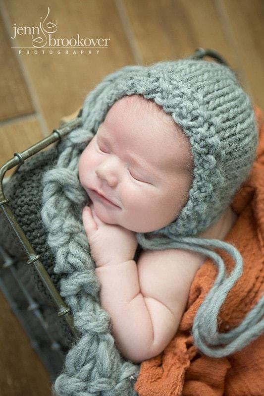 newborn boy in gray knitted cap and orange wrap