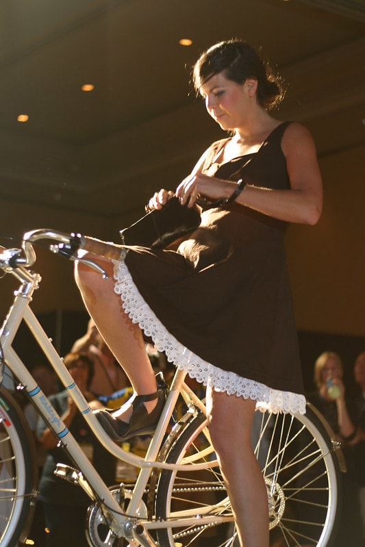 Woman in a skirt mounting a step-through bike