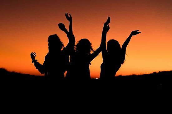 women dancing at sunset