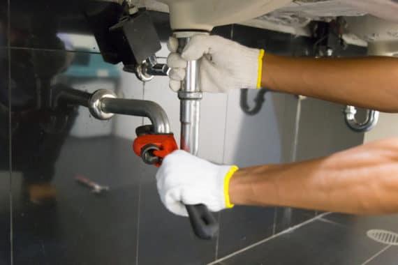plombier reparant les tuyaux de l'evier